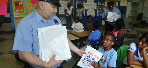 Police Officer handing Child Literature
